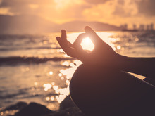 Yoga Concept.  Silhouette Woman Hand Practicing Lotus Pose On The Beach At Sunset.