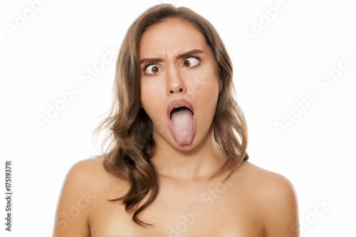 Photo Portrait of beautiful young woman making funny faces on white background