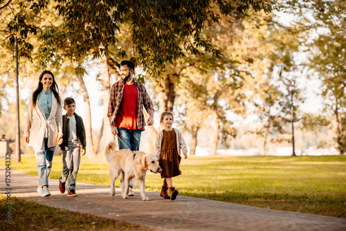 Family walking in park with dog Fototapet