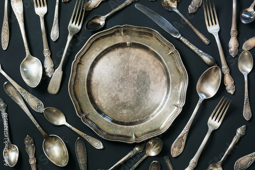 Plate, spoons, forks, knives, silverware pattern on black background. Kitchen texture.