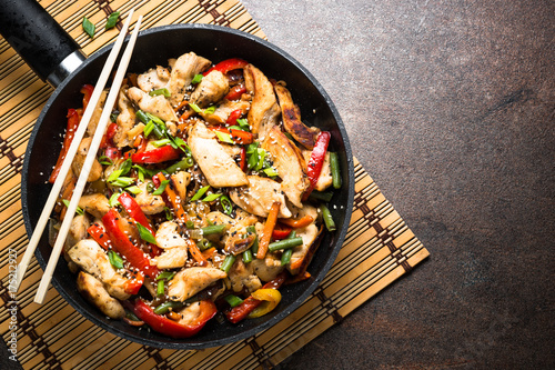 Photo Chicken stir fry with vegetables at stone background