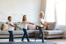Candid Shot Of Three Cute Children Wearing Similar White T-shirts And Blue Jeans Walking Barefooted On Floor At Home While Dancing Or Doing Conga Line Indoors On Birthday Party, Having Happy Faces