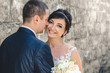 Fashionable close-up portrait of the bride and groom against the background of the wall of the old castle. Wedding day. Bride hugs groom.