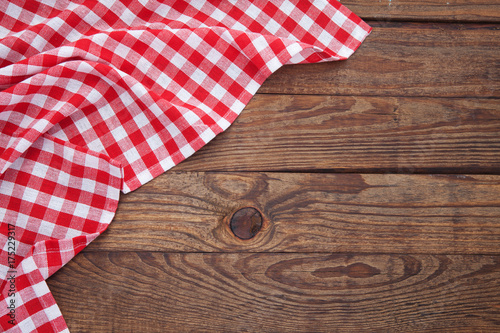 Old vintage wooden table with a red checkered tablecloth. Top view mockup.