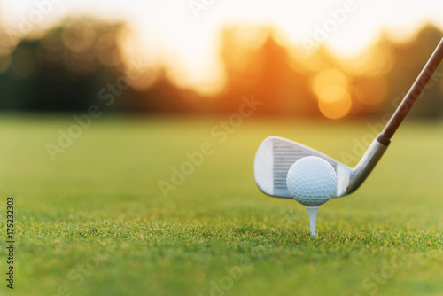 Spoed Foto op Canvas Golf The golf club behind the golf ball on the stand. Against the background of grass and sunset