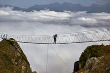 Man Walking On Suspension Bridge And Looking At Cloudy Mountains Below.