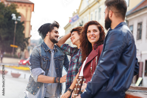 Fototapety, obrazy: Group of young friends hangout on city square .
