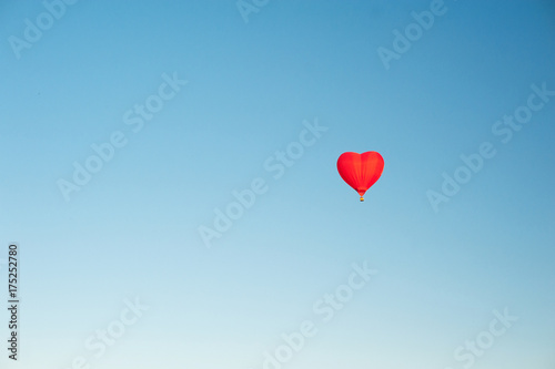 Red hot air balloon in the shape of a heart in clear blue sky. Aerostat over the field landscape.  Close up