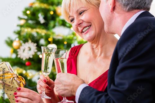 Plakat Starszy mężczyzna i kobieta obchodzi Wigilia z lampką wina musującego