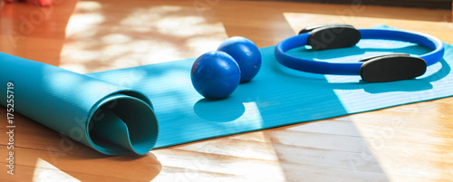 Photo  Yoga mat and exercise weights on wooden floor