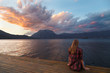 Travel, tourism and people concept - single woman is sitting near clean lake and looking at sunset