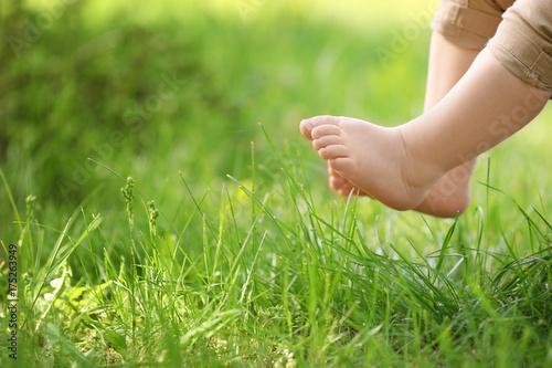Obraz Little child and green grass in park - fototapety do salonu