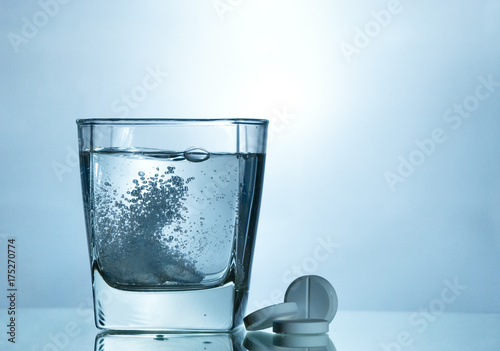 Photo Effervescent tablet in a glass with bubble