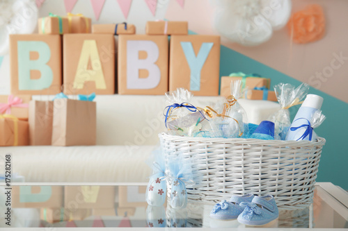 Fotografía  Wicker basket with gifts for baby shower party on table indoors