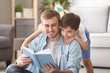 Young man and his little son reading book at home