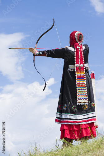 Photo  archery girl shoots in ethnic ancient clothes