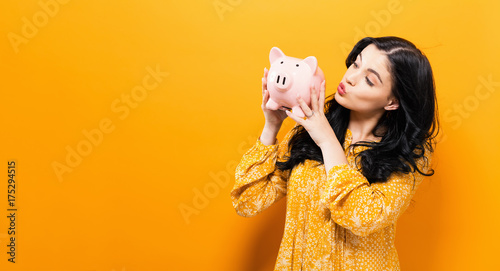 Fototapeta Young woman with a piggy bank on a yellow background obraz