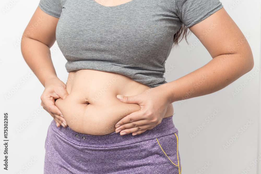 Fototapeta Overweight woman hand pinching excessive belly fat on gray background, Healthy concept