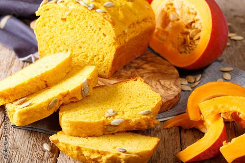 Foto auf AluDibond Brot Fresh baked pumpkin bread on wooden board with seeds. horizontal