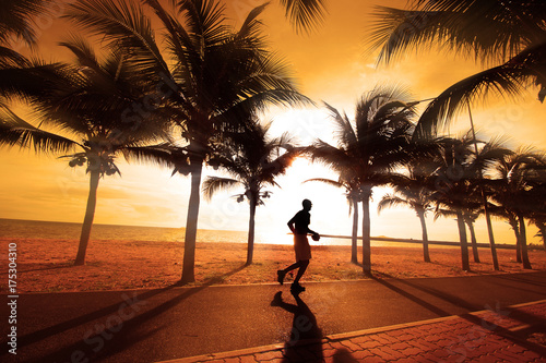 Poster Lieu connus d Asie Sillouette of the man jogging. The coconut trees on the beach at sunset.