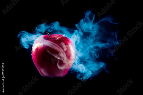 Photo  poisoned apple with dramatic lighhting on a black background