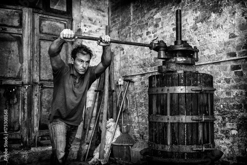 Fotografía  Shirtless winemaker farmer working on a traditional wine press