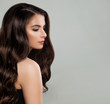 Portrait of Pretty Young Woman Fashion Model with Stylish Hairstyle. Makeup and Long Healthy Wavy Hair on Gray Background