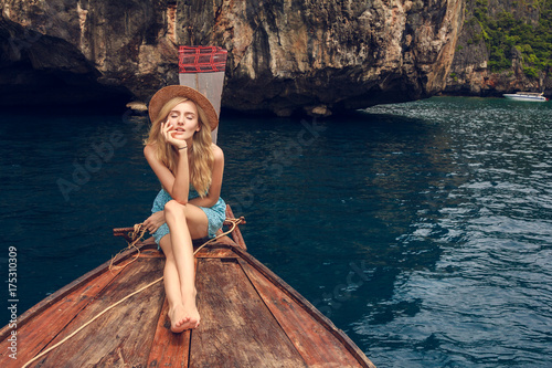 Fototapeta Young beautiful blonde girl cruising on retro wood boat by Andaman sea and behind her you can see Ko Phi Phi Lee Island in full glory. Dressed in beautiful blue dress and wearing straw hat.  obraz na płótnie