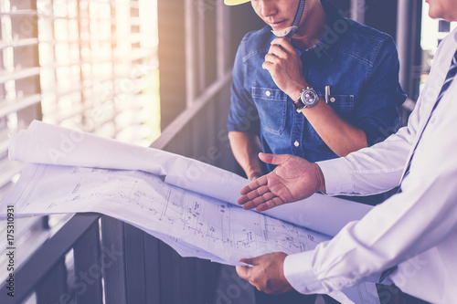 Fotografía  contractor and engineer with blueprints discuss at a modern construction site, Architecture and Engineering concept