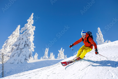 Tablou Canvas Skier skiing downhill in high mountains against blue sky