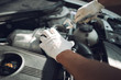 Close-up. A man is fixing a car with a wrench. White car. White gloves for repair