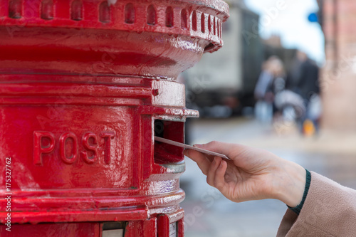 Throwing a letter in a red British post box Fotobehang