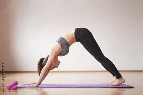 Plakat Piękna i zdrowa młoda sporty kobieta w sportswear robi joga w lekkim pokoju na macie