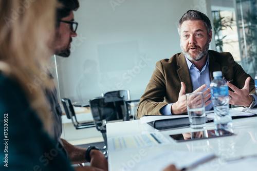 Businessman explaining new business ideas to peers Canvas Print