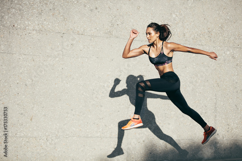Fit young woman jumping and running