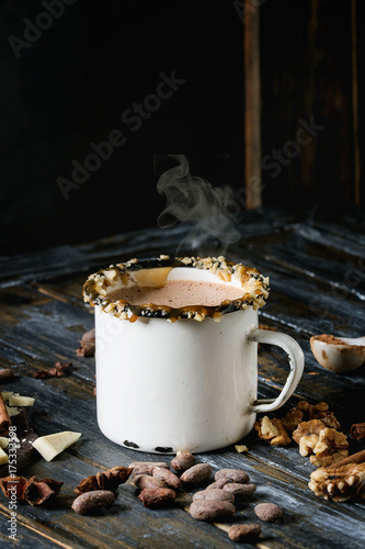 Foto op Plexiglas Chocolade Vintage mug of hot chocolate, decor with nuts, caramel, spices. Ingredients above. Chopped dark and white chocolate, cocoa beans, anise over old wooden table. Dark rustic style