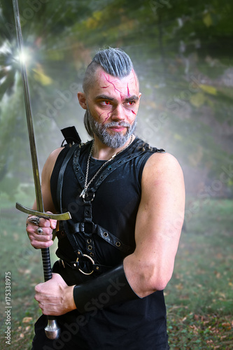 Photo Cosplayer dressed as character Geralt from Rivia from game Witcher,  poses durin
