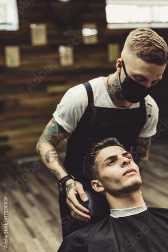 Crop stylist preparing young tattooed man in chair for shaving in barbershop Canvas Print