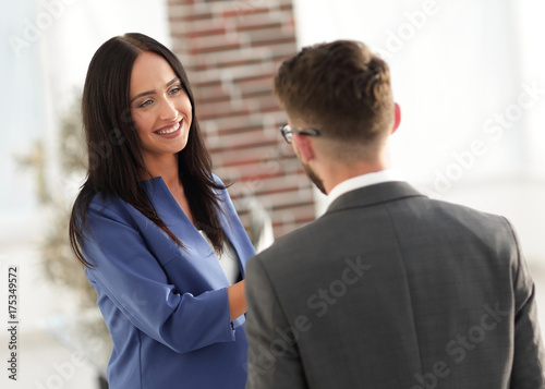 Smiling businesswoman communicating with male colleague in the o Wallpaper Mural