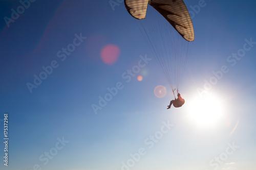 Plakat Paralotnia leci w błękitne niebo.