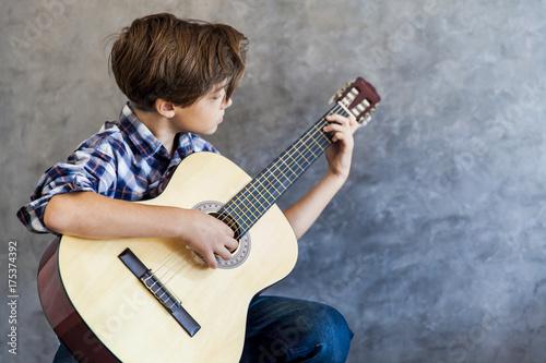 Plakat Śliczny nastoletni chłopak bawić się acustic gitarę
