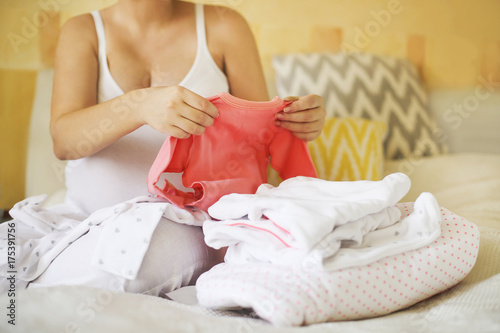 Pregnant woman is packing baby clothes Canvas Print