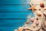 Fototapeta See - beach scene concept with sea shells and starfish on a blue wooden background