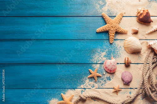 Spoed Fotobehang Strand beach scene concept with sea shells and starfish on a blue wooden background