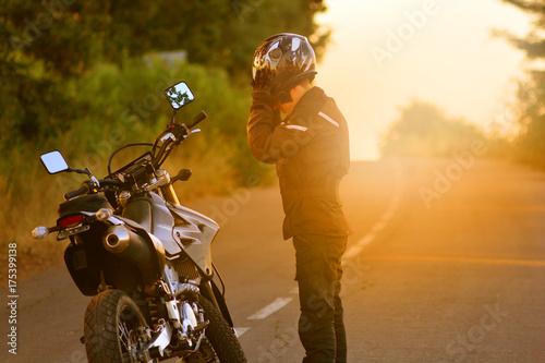 Fototapeta Motocyklista zatrzymuje się i zdejmuje kask