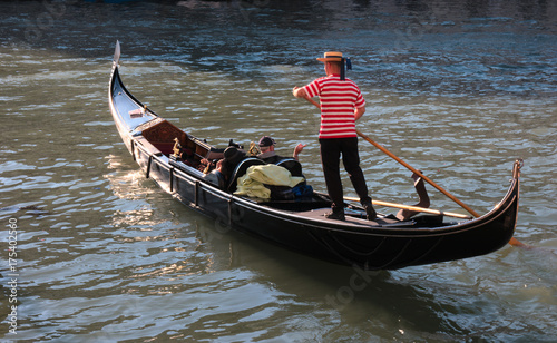 Gondola and gondolier in Venice / A typical and iconic image of Venice, Italy, a Gondolier leads his gondola with two tourists on a beautiful sunny day
