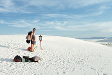 Man Walking In Desert With Camping Gear