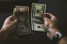 Close-up Of A Man Hands Counting A US Dollar Bills