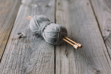 Grey Ball Of Wool With Bamboo Needles On Rustic Wood Table