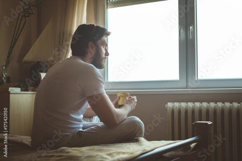Fotografie, Obraz  Young handsome man drinking morning coffee in the bed